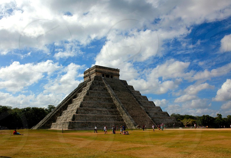 people standing near aztec temple under white clouds and blue sky photo