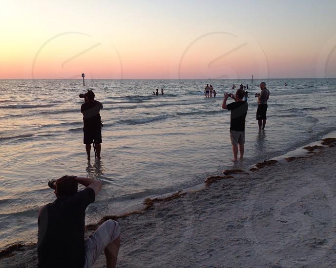 man taking photo on white sand beach photo