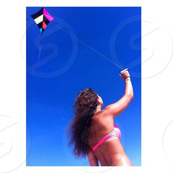 woman in pink brassiere playing kite photo