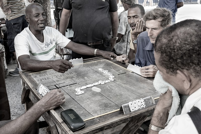 A group of cuban men play dominos together as tensions run high during a game in Santiago de Cuba Cuba. photo