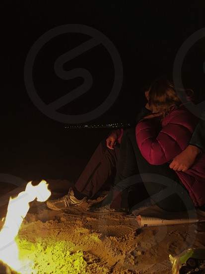 woman wearing red bubble jacket and black pants beside man wearing black pants and gray Nike shoes near bonfire during nighttime photo