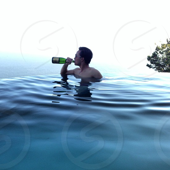 man on water drinking wine photo