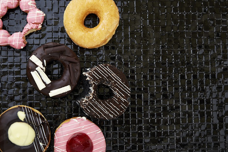 Multi-colored assortment Office Building donuts with sprinkles and frosting on dark  background  photo