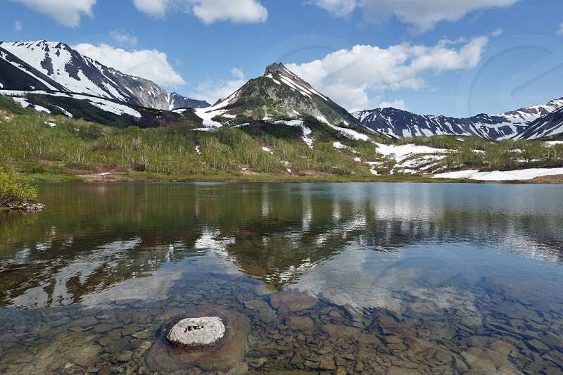 Summer landscape of Kamchatka Peninsula: beautiful view of Mountain Range Vachkazhets mountain lake and clouds in blue sky on sunny day. Eurasia Far East Russia Kamchatka Region. photo