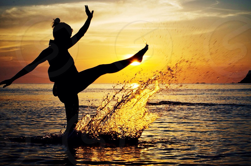 silhouette of woman kicking right foot on body of water during sunset photo