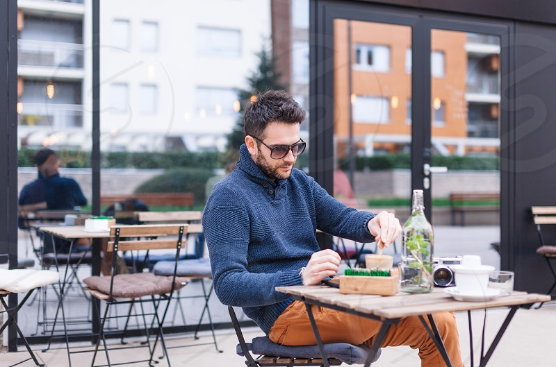 Man in a coffee shop sitting in the terrace outdoors photo