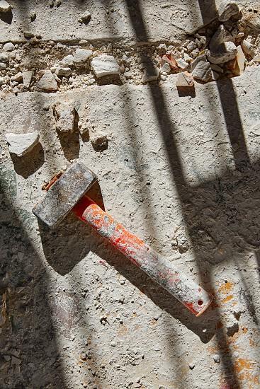 Mason vintage hammer tool on debris background in house improvement photo