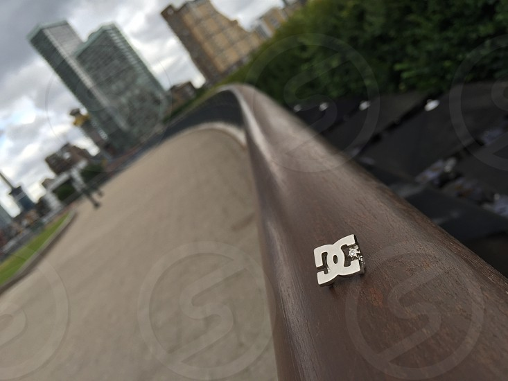 silver DC Shoes emblem on top of brown balustrade photo