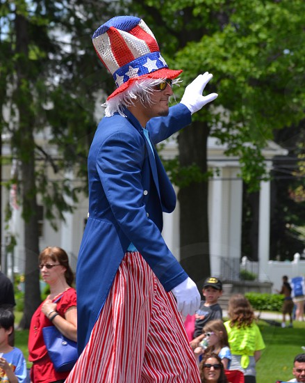 man wearing uncle sam costume walking in a parade photo