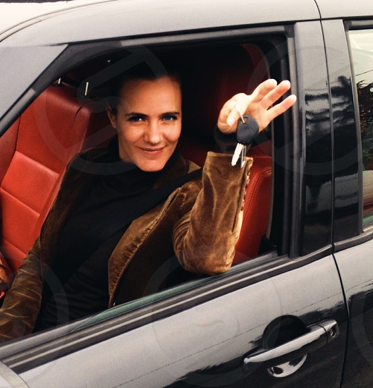 woman sitting inside car and holding car key photo
