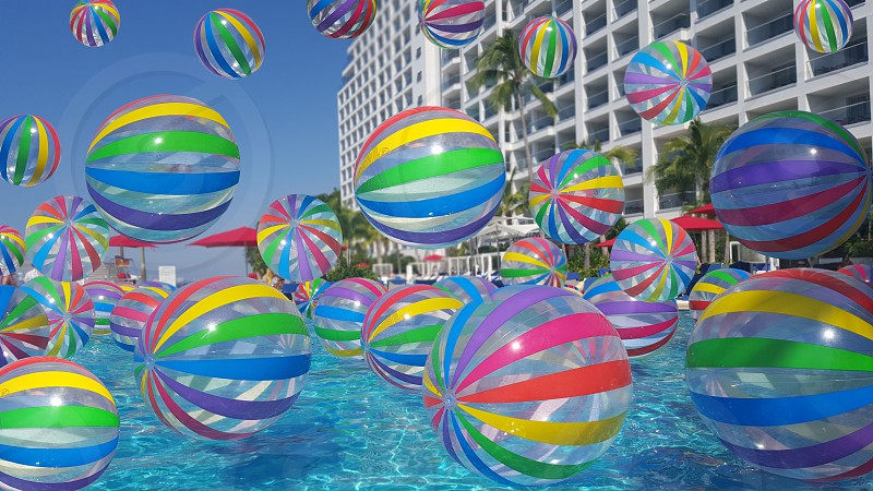 Beach balls floating on the surface of a pool during a pool party photo