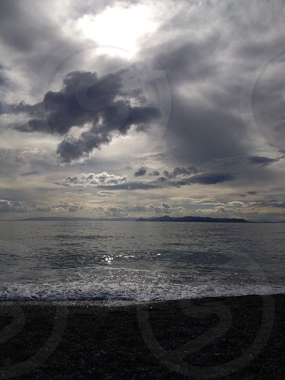 ocean and beach with cloudy sky photo