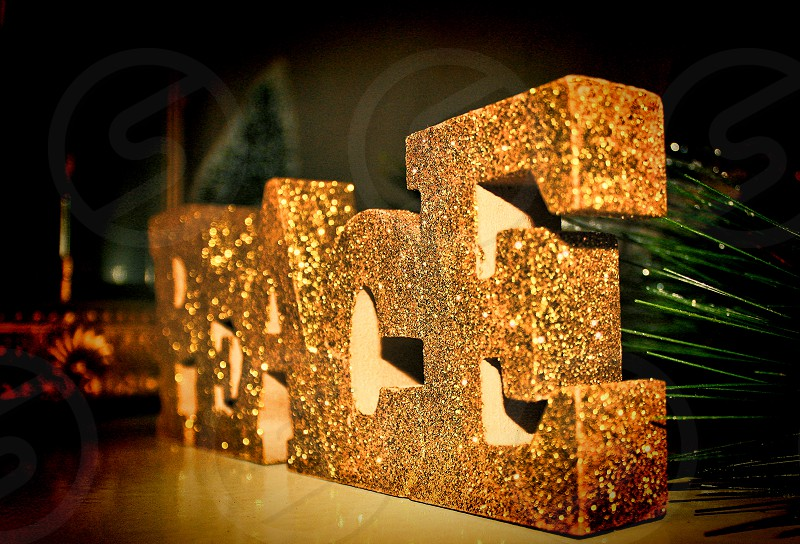 The word 'Peace' in gold and glitter on a Christmas mantlepiece. photo
