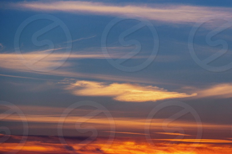 blue sky with orange streaks and white clouds photo