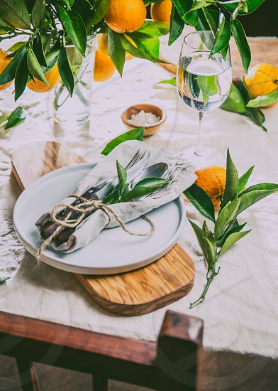 Table setting with white plate cutlery linen napkin and orange tree branch decoration on white linen tablecloth . Close up. Table with table setting and shair. photo