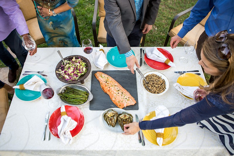 Friends Drinking red wine celebrating an Anniversary forties Fifties food salmon salad artichoke healthy asparagus table setting photo