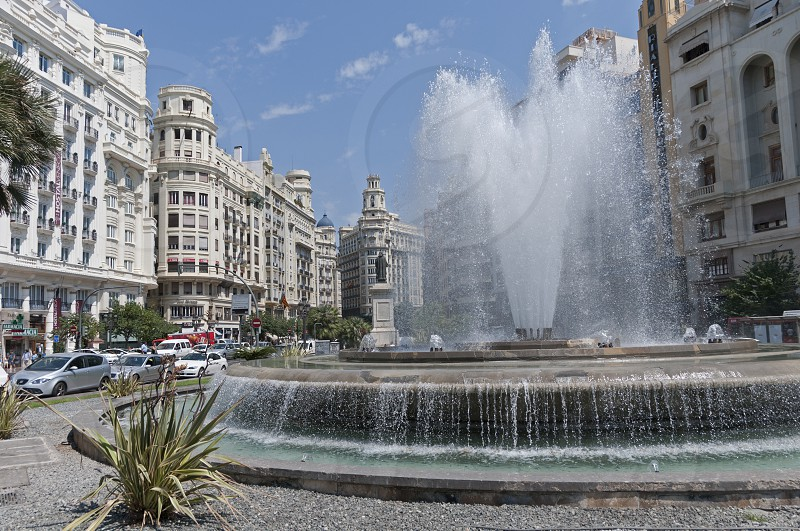 A fountain in a Spanish city square. photo