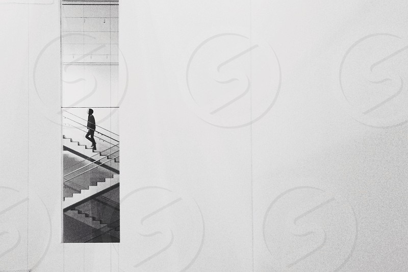 man on spiral stairs negative photography photo