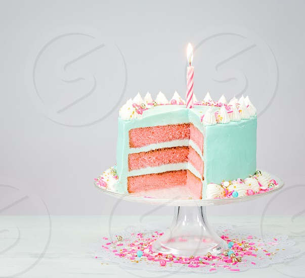 Pastel blue birthday cake over white background with pink layers and sprinkles. photo