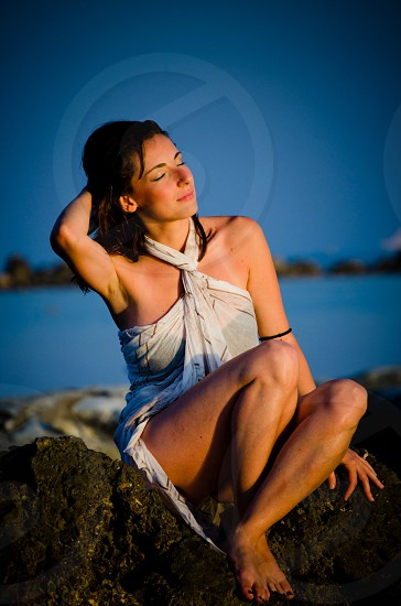 woman in brown lined white halter top dress closing her eyes while holding her hair and sitting on black rock photo