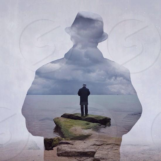 Man wearing black formal suit standing brown stone seashore view photo