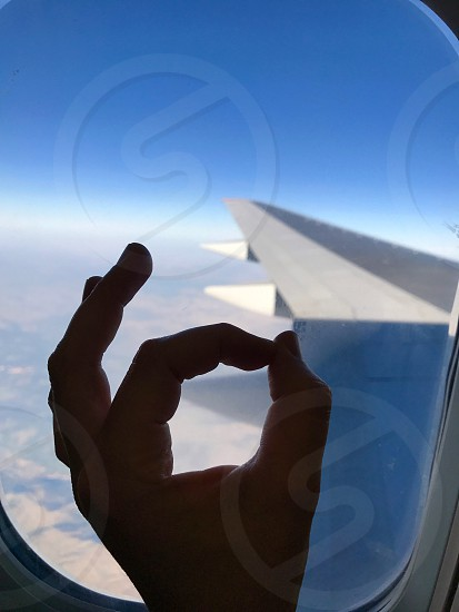 Hand fingers crossed okay adventure flying plane illuminator gesture travel flight vacation  photo
