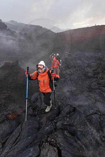 TOLBACHIK VOLCANO KAMCHATKA PENINSULA RUSSIAN FAR EAST - JULY 27 2013: Group of tourists hiking on the new lava field eruption Tolbachik Volcano on Kamchatka Peninsula. Klyuchevskaya Group of Volcanoes. photo