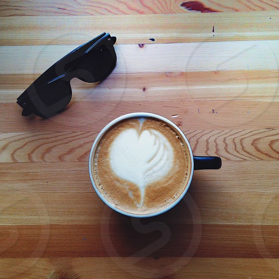 black retro square sunglasses near hear foam latte in mug on table photo