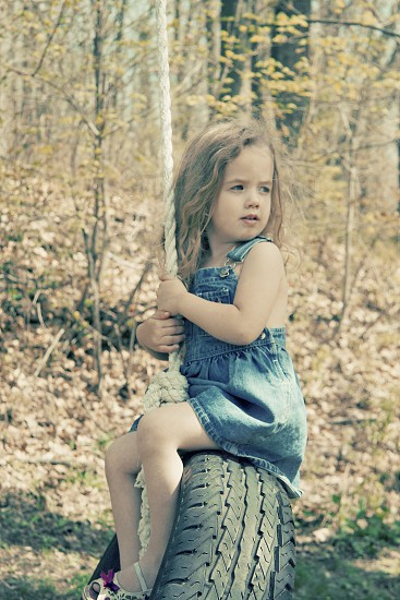 little girl on old fashioned tire swing photo