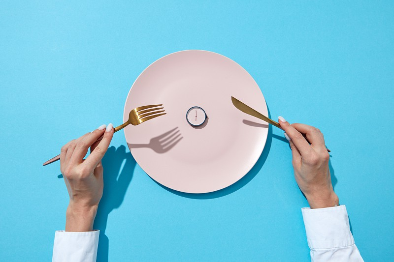 Round watch of six o'clock and woman's hand with fork and knite in agirl's hands on a blue background with shadows. Time to lose weight eating control or diet concept. Place for text. photo