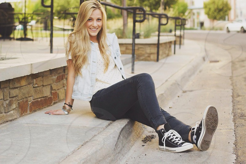 woman wearing white denim jean jacket and gray leggings with black high top converse sneakers photo