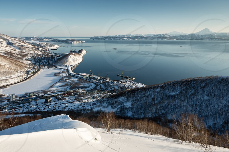 Beautiful winter Kamchatka landscape: top panoramic view of the Petropavlovsk-Kamchatsky City Avachinskaya Bay and Pacific Ocean at sunset. Russia Far East Kamchatka Peninsula. (Evening lighting.) photo