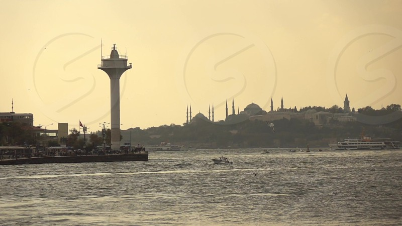 Picturesque wiews of the historical part of old sity Istanbul with antique mosques and sea lighthouse on a background of sunset sky. Slow motion Full HD video 240fps 1080p. photo
