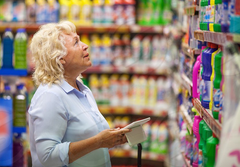 Senior woman with tablet computer in the store. She looking at detergents in the section of household chemicals photo
