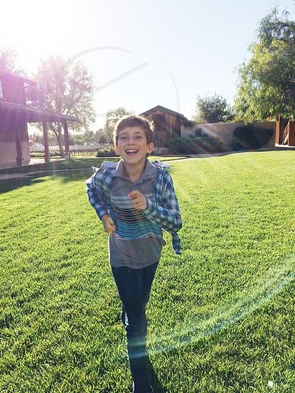Boy running toward camera with sun flare. Green grass barn play male photo