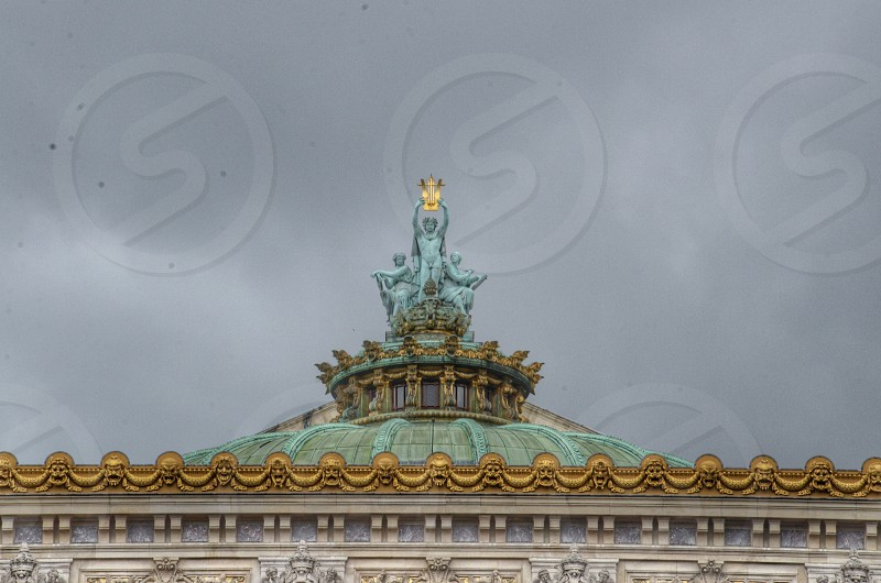 person holding up golden harp sculpture on top of building photo