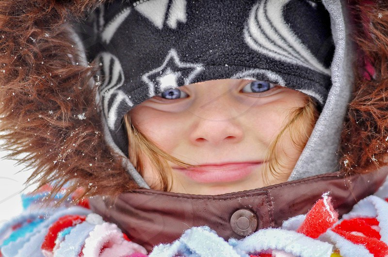 Young girl blue eyes winter bundled face hat scarf cold snow  photo