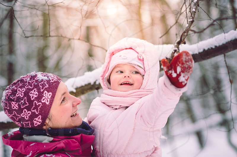Mother spending time with her little daughter outdoors in the wintertime photo