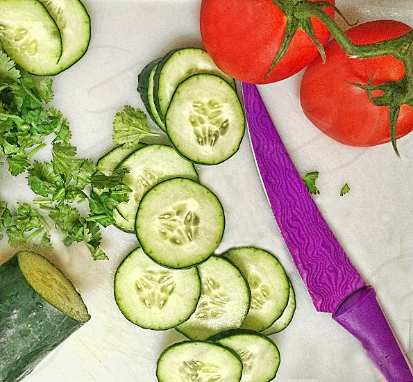 Looking downward at a cutting board with a knife sliced cucumbers and tomatoes photo