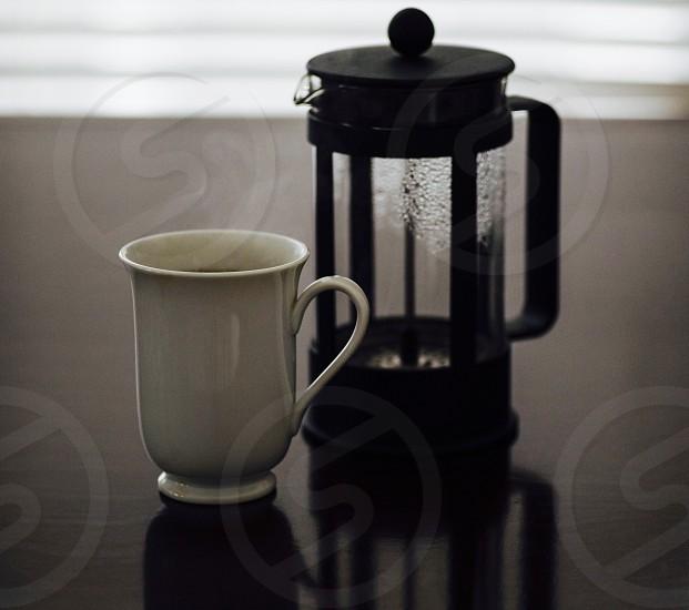 white ceramic mug beside black french press photo