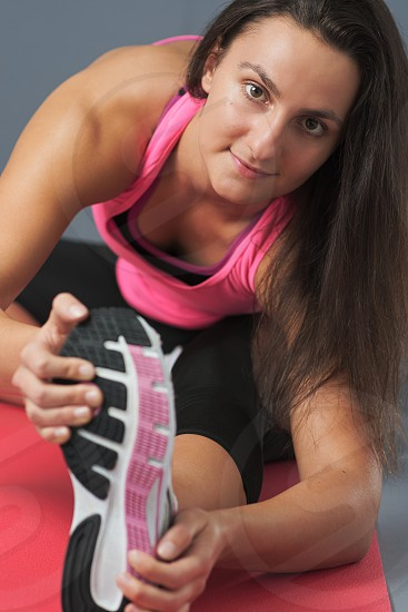 Young Beautiful Sporty Woman Stretching on Pink Yoga Mat photo