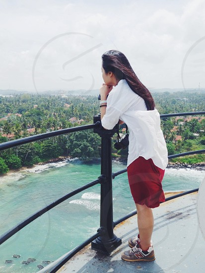 woman in white 3/4 sleeved shirt leaning on black metal railings photo