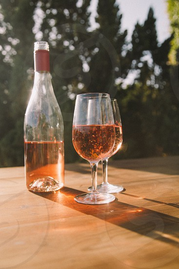 two wine glasses filled with rose wine on a wood table next to the bottle surrounded by trees under the sun photo