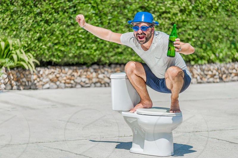 The bearded man in goggles astride the toilet which is installed in the middle of the street. Toilet brush in his hand cooking pan on his head. Drinking beer photo