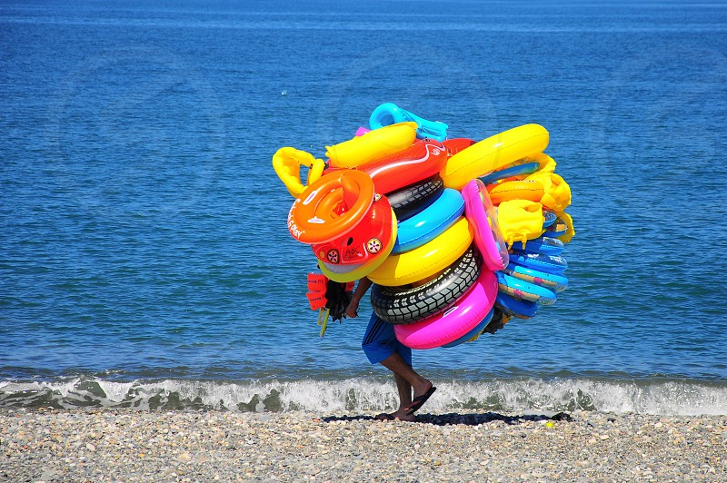 person carrying many colorful swim tube rings on beach photo