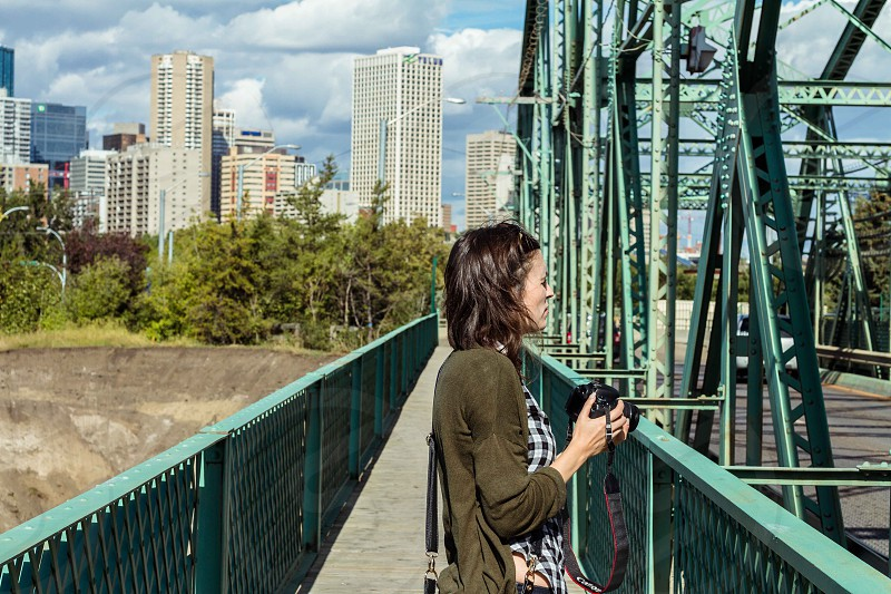 woman standing on green footbridge holding black camera photo