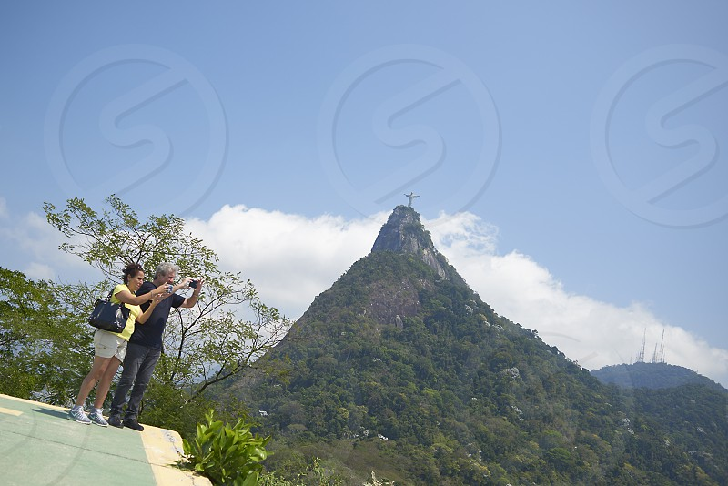 A couple of tourists taking pictures of the mountain with the Christ the Redeemer statue on top of it in Rio de Janeiro Brazil photo