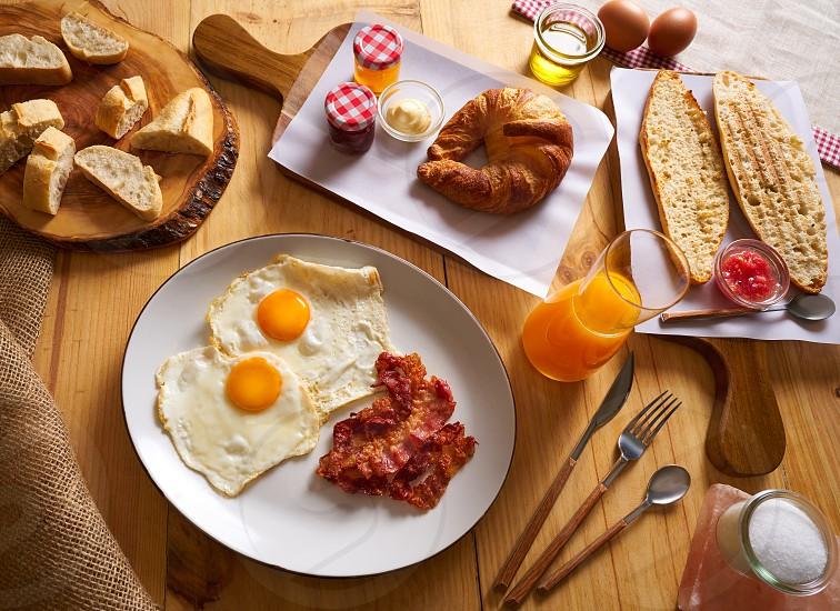 Continental breakfast croissant eggs bacon bread slices orange jiuce photo