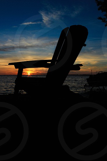 sunset sky over a adirondack chair silhouette photo