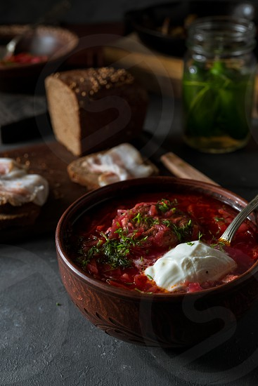 Russian borscht soup rye bread and smoked bacon on a dark rustic background photo